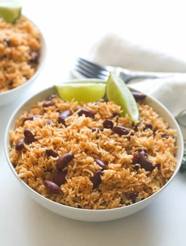 Caribbean rice and beans in a white bowl garnished with sliced lime