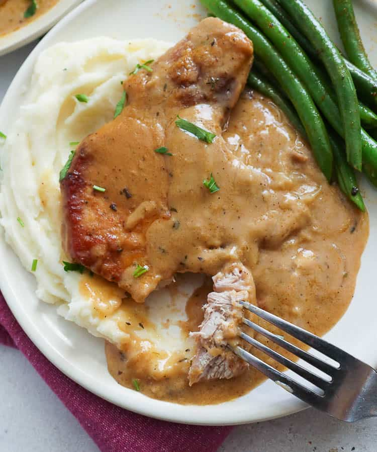 Mashed Potatoes topped with Smothered Pork Chops and Green Beans on the Side