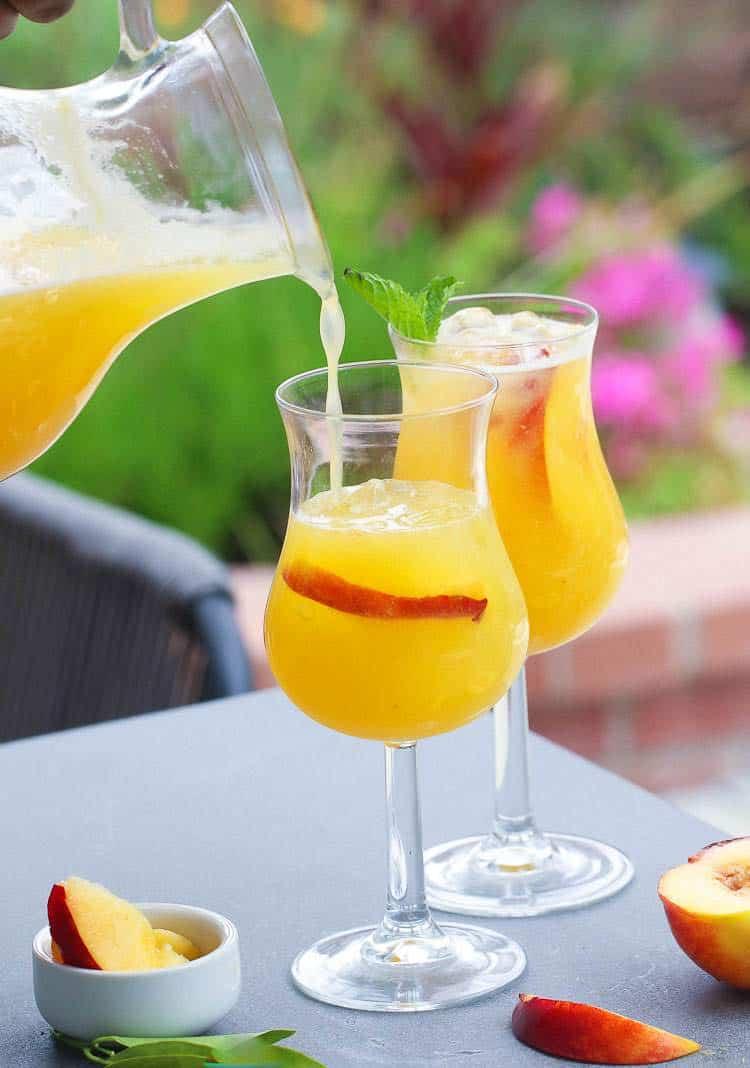Pouring Peach Bellini in a fancy glass