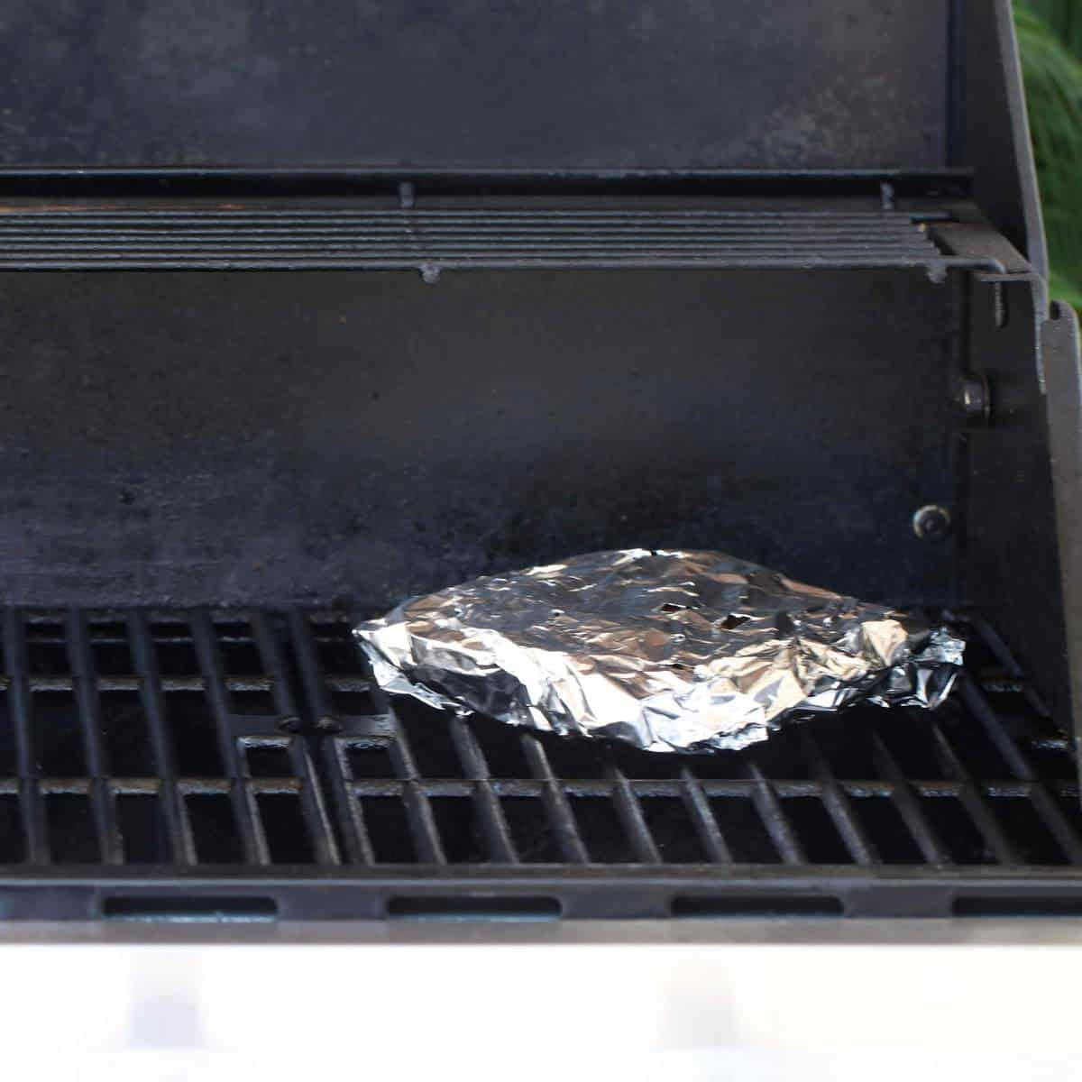 chunks of wood wrapped in a foil paper on the grill for smoking