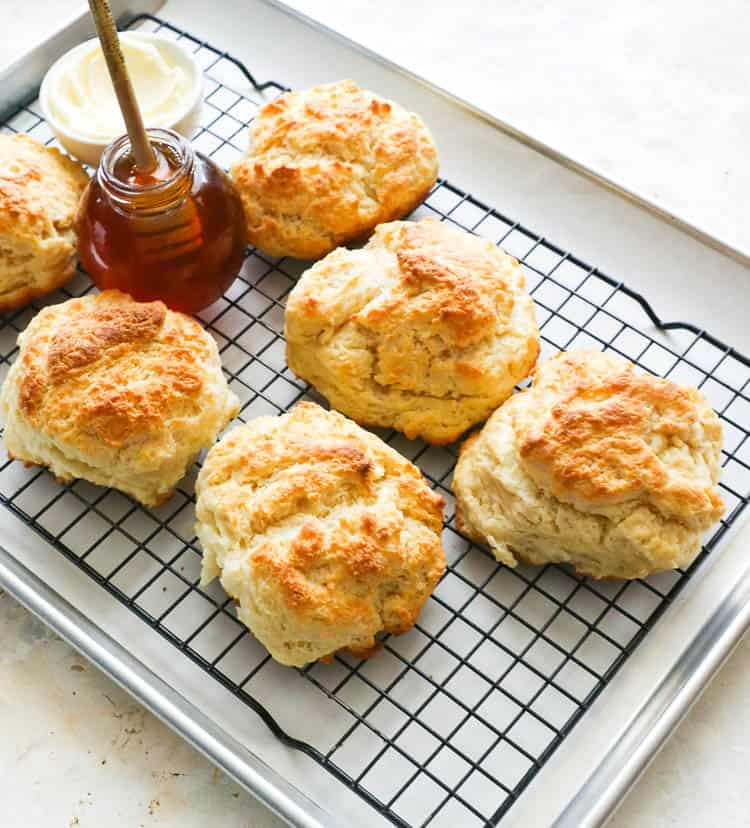 Cathead Biscuits on a cooling rack with honey and butter