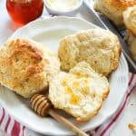 Biscuits with honey dipper on a white plate