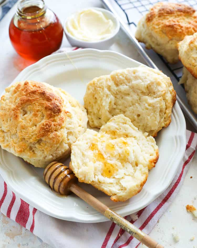 Cathead Biscuits with honey dipper on a white plate