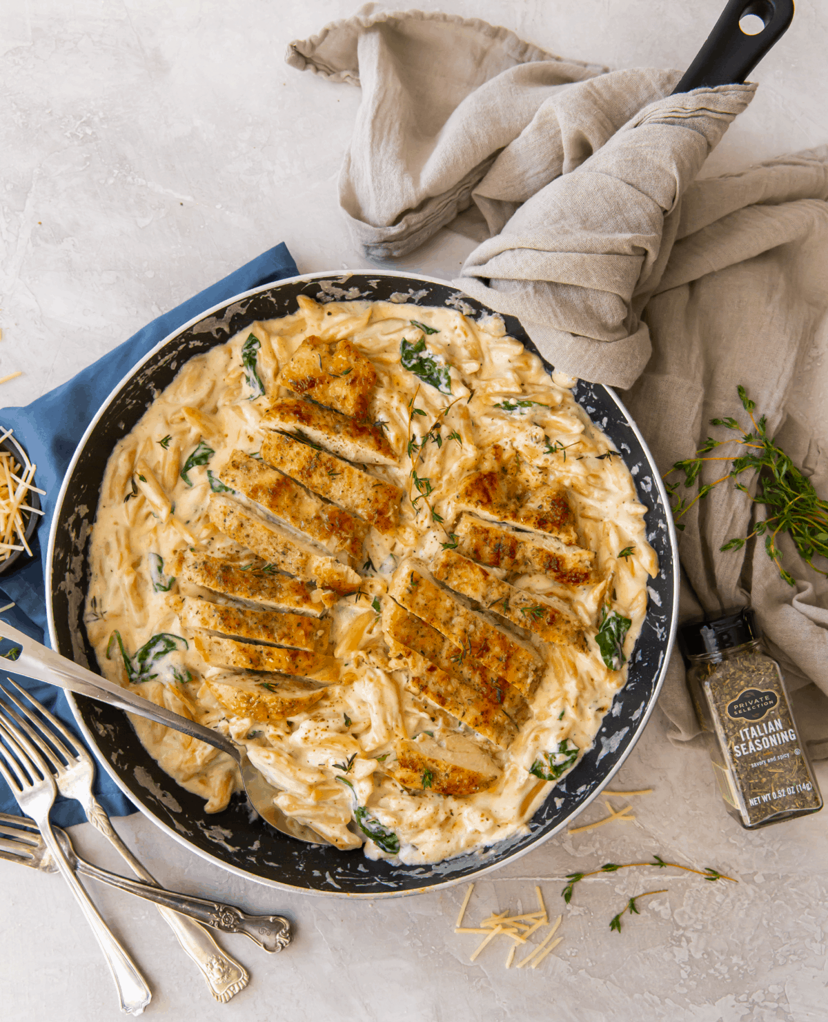Chicken on a bed of pasta and alfredo sauce in a black pan