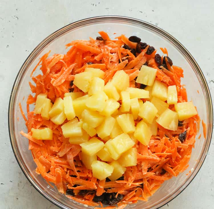 carrots, pineapple chunks, raisins in a bowl ready for mixing