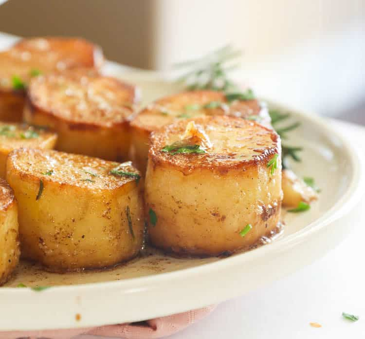 Close-up Side Shot of Fondant Potatoes in a White Plate