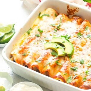 chicken enchiladas on a white baking this with slices of avocado on top