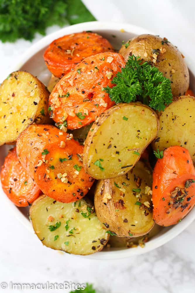 A bowl of Roasted Potatoes and Carrots topped with veggies