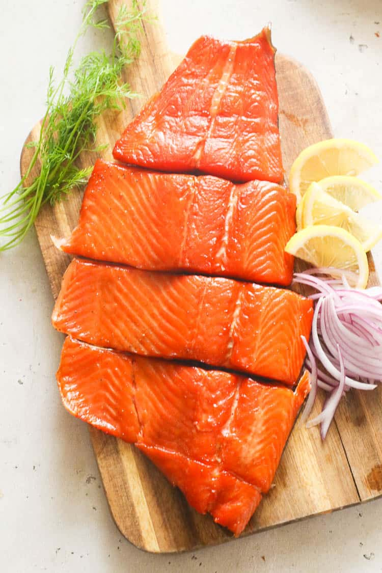 salmon on achopping board with lemon wedges, onion slices, and thyme