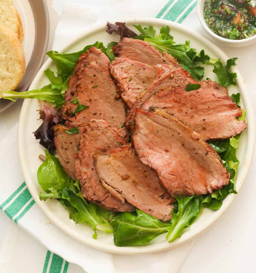 sliced beef on a bed of greens