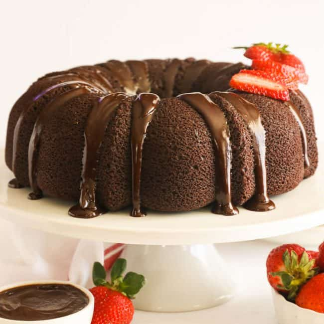 Chocolate Pound Cake on a white cake stand with sliced strawberries on top