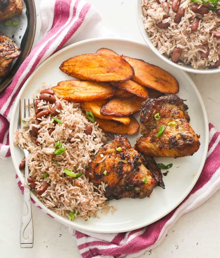 Jamaican rice and beans with chicken and fried plantains on a plate