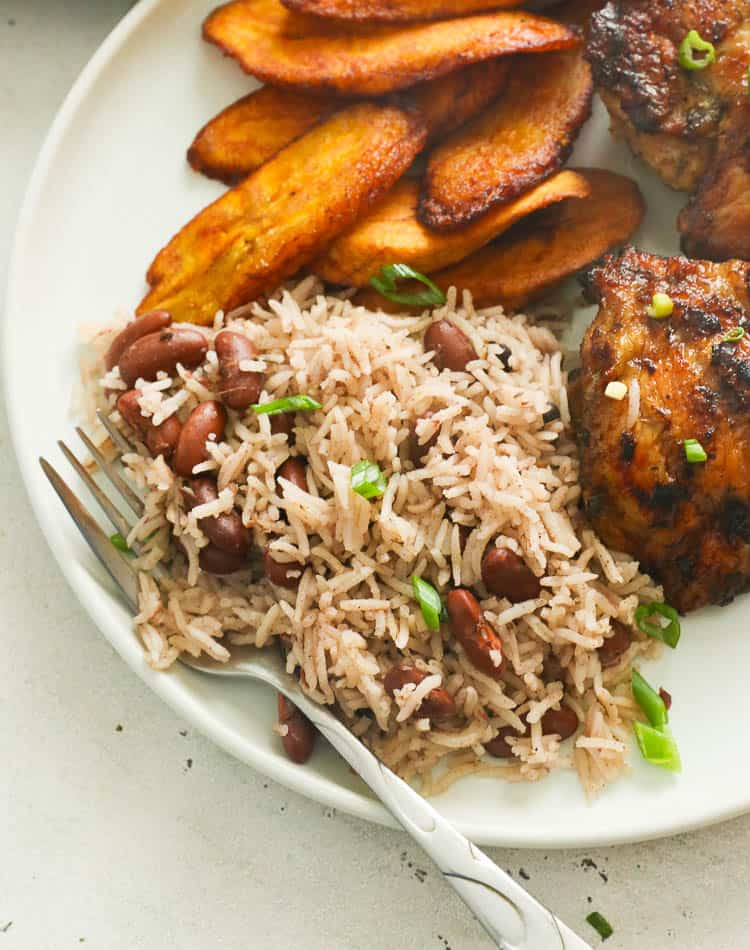 jamaican rice and peas served on a white plate with chicken and fried plantains