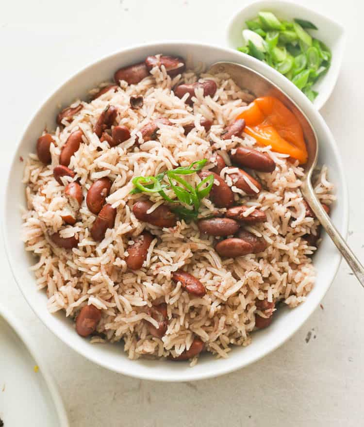 Jamaican rice and peas with green onions toppings on a bowl