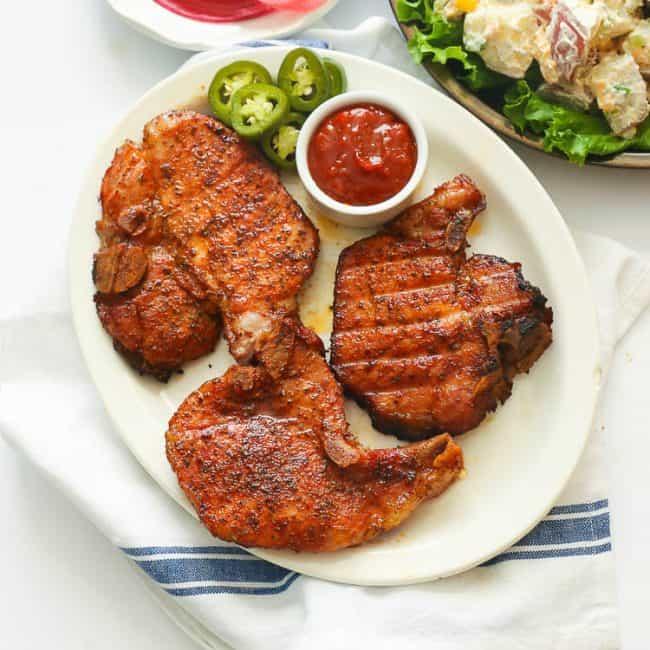 Three pork chops on a white plate