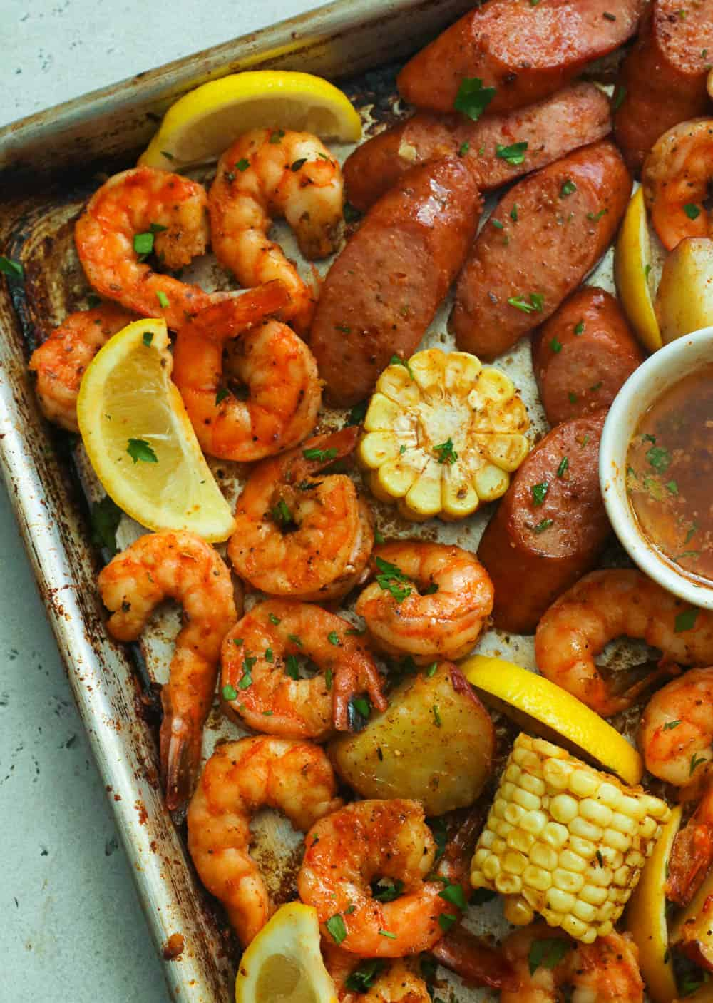 Cajun shrimp and sausage boil garnished with cilantro and lemon slices