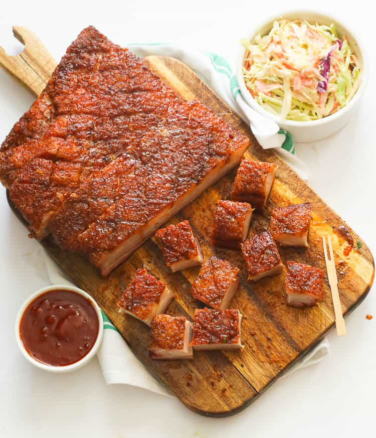 Top view of smoked pork belly on a chopping board with coleslaw