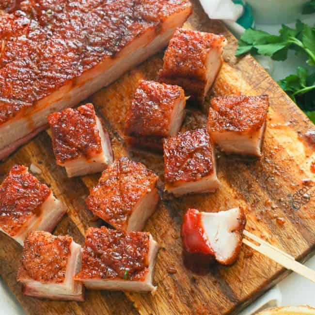 chopped pork belly on a wooden chopping board