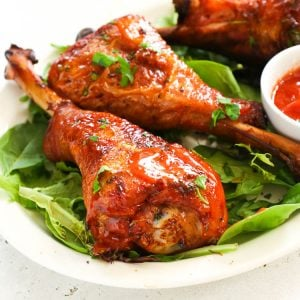 smoked turkey legs garnished over greens with sauce