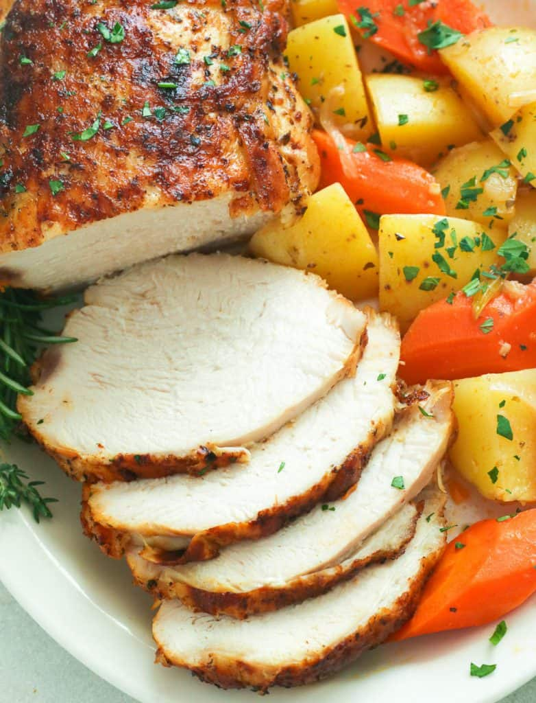 Sliced instant pot turkey breast with roasted carrots and potatoes