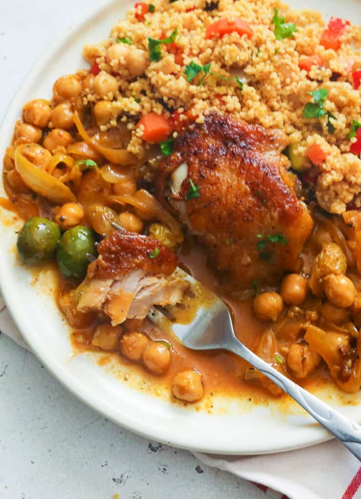 Chicken Tagine Served with Couscous on a White Plate